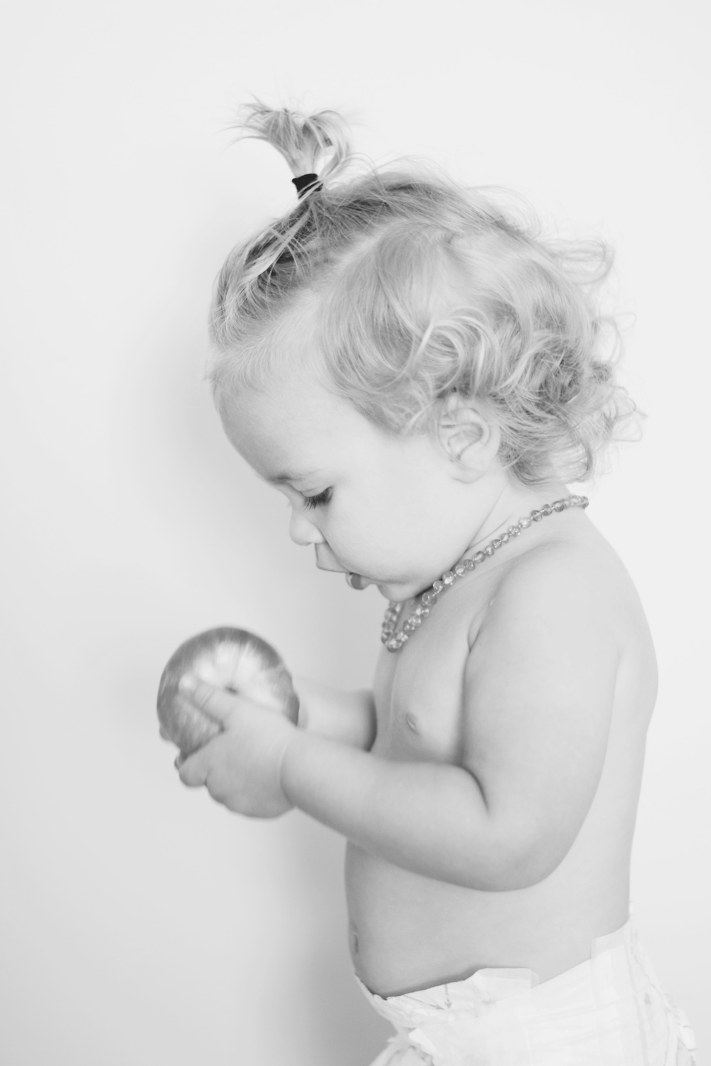 rocco eating an apple, wearing a manbun, being photographed by his sister